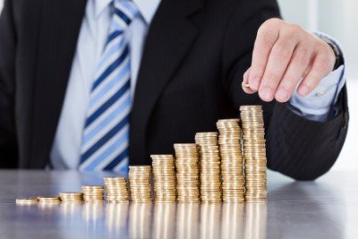 20509285 - close-up of businessman hand put coins to stack of coins