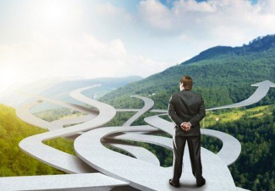 34924011 - businessman stands choosing his way on nature background